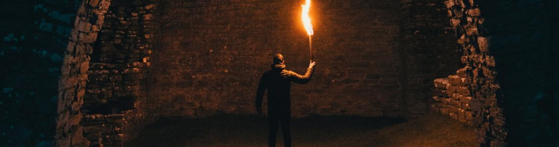 Mysterious dark tunnel. Man facing wall with torch.