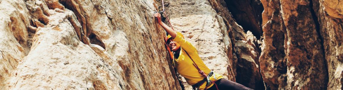 Climber reaching across a chasm.
